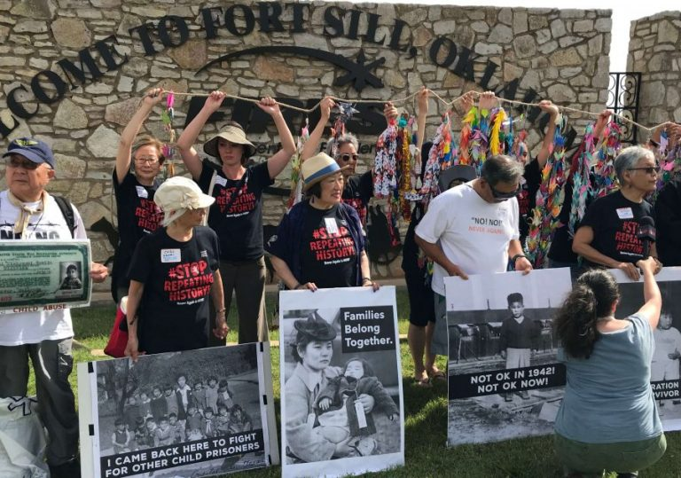 Japanese American camp survivors stand in front of Fort Sill Gate with protest signs and paper cranes