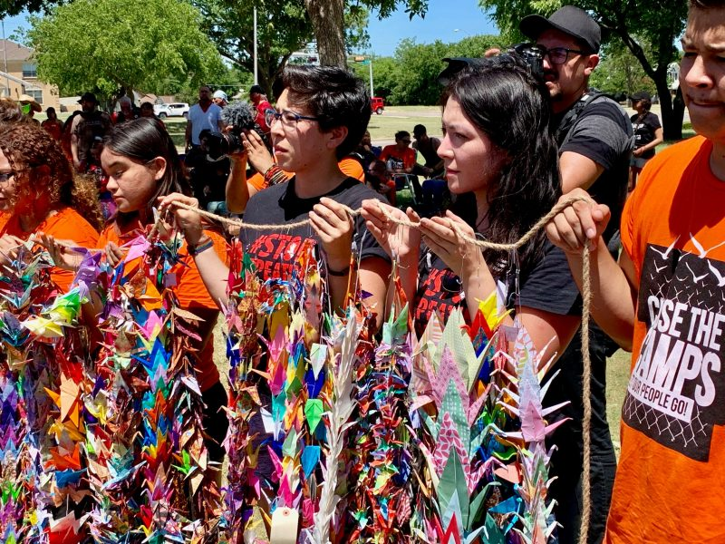 Yonsei and Dreamers hold up tsuru strands during healing ceremony in Fort Sill, Oklahoma protest