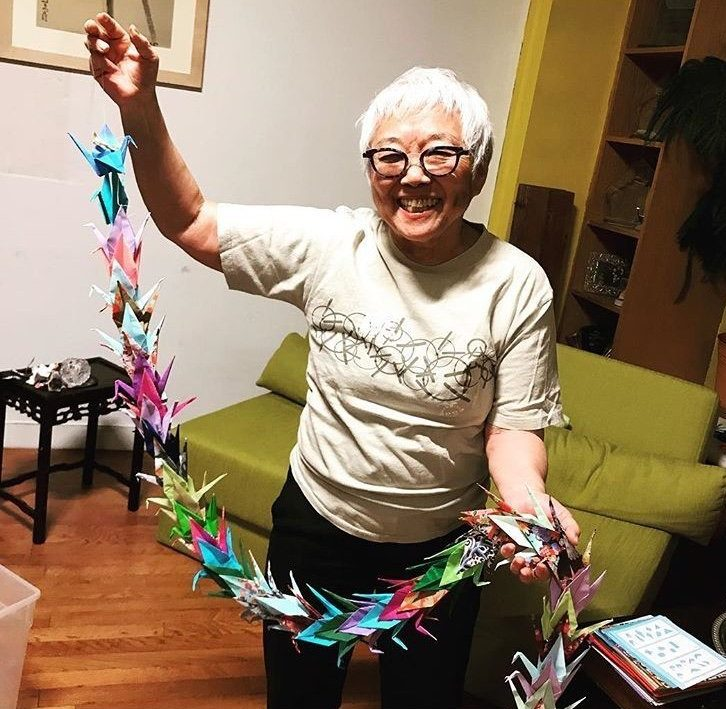 New York-based Japanese American Theodora holds up a chain of paper cranes