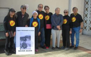 "Photo by Kathy Kojimoto of protestors outside Yuba County Jail holding protest sign ""Never Again"""
