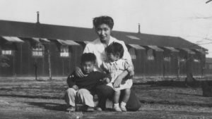 Satsuki and her brother stand with their mother inside a U.S. Concentration Camp