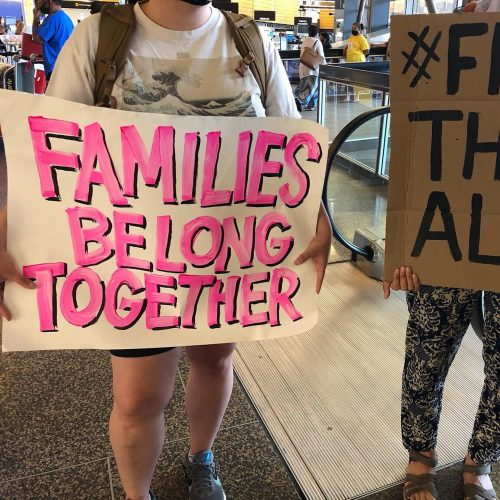 "close up of protest sign at Sea Tac Airport that says ""Families Belong Together"""