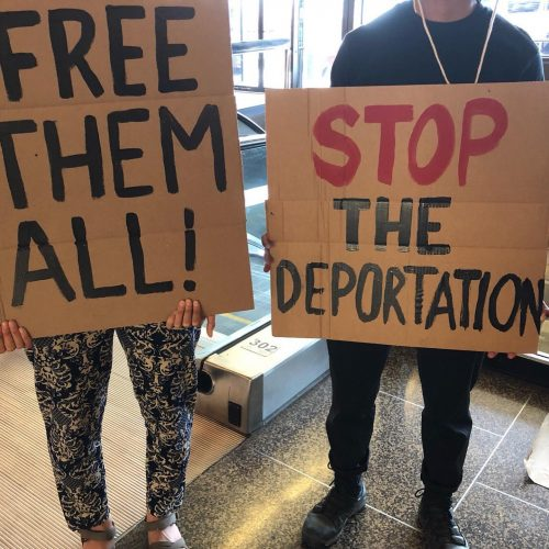 "Sea Tac Airport protest ""Free Them All"" and ""Stop the Deportation"" signs"