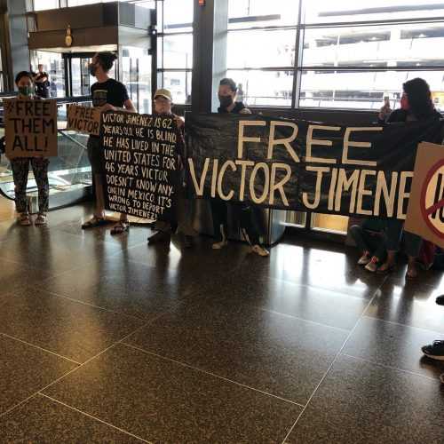 "Protestors hold up banner reading ""Free Victor Jimenez"" at Sea Tac Airport"